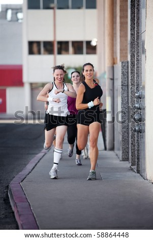Group of women racing down a city street for fun. - stock photo