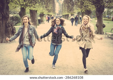 Group of women running at park in Copenhagen. They are in their twenties and they are wearing smart casual clothes. Happiness, friendship and lifestyle concepts. - stock photo