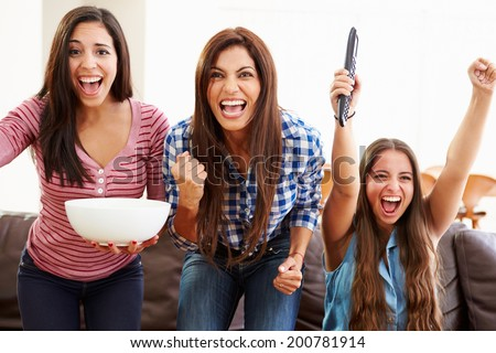 Group Of Women Sitting On Sofa Watching Sport Together - stock photo