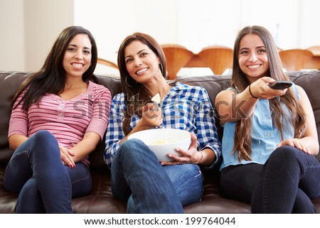 Group Of Women Sitting On Sofa Watching TV Together - stock photo