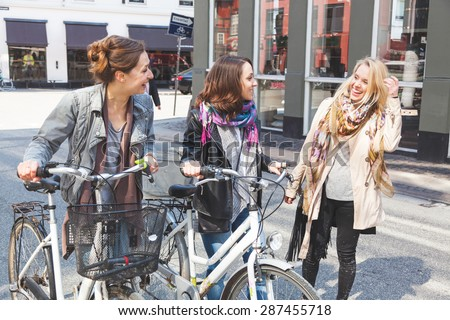Group of women walking in Copenhagen. They are in their twenties and they are wearing smart casual clothes. Two of them are holding a bicycle, typical mode of transport in Denmark. - stock photo
