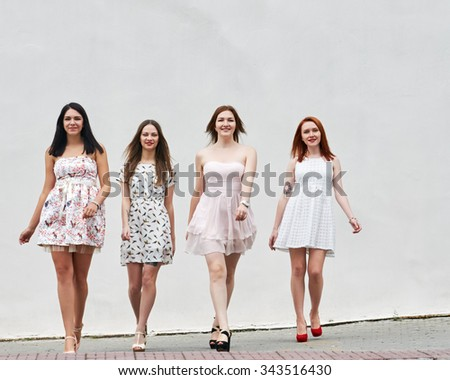 Group Of Women Walking On City Street about light wall - stock photo