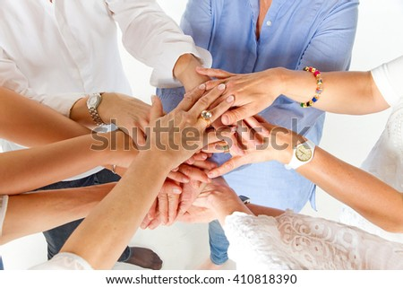 Group of women with hands together showing unity - stock photo
