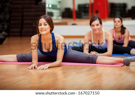 Group of women working on their flexibility and doing some leg splits in a gym - stock photo