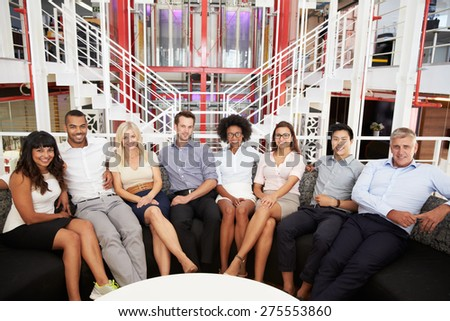 Group of work colleagues sitting in an office lobby - stock photo