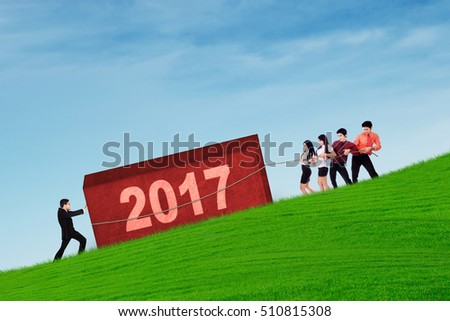 Group of worker tries pulling a boulder with number 2017. Symbolizing of workers collaborate for their success