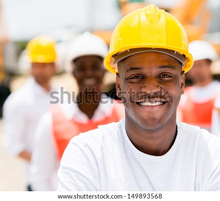 Group of workers at a construction site smiling  - stock photo