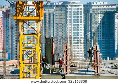 Group of workers at construction site on a top of a building - stock photo