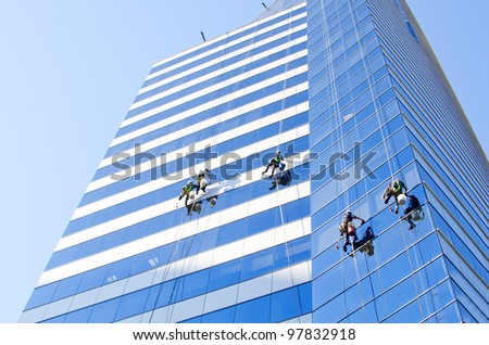 Group of workers cleaning windows of a tall building at Santiago de Chile - stock photo