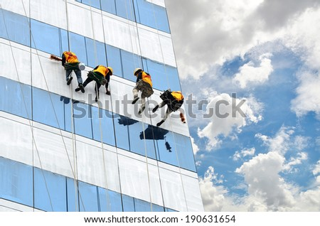 group of workers cleaning windows on high rise building - stock photo
