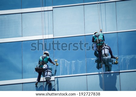 group of workers cleaning windows service on high rise building - stock photo