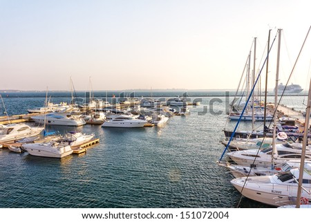 Group of yachts and boats in the harbor in sunrise - stock photo