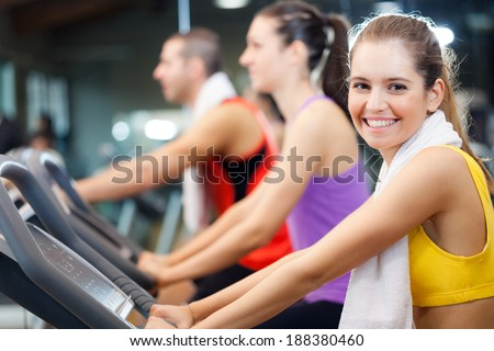 Group of young active people doing fitness in a gym - stock photo