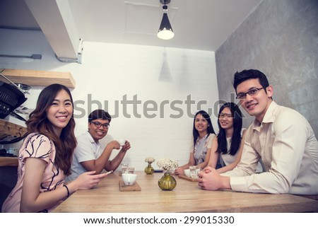 Group of young adult talking and meeting together in coffee shop. - stock photo