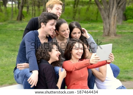 Group of young adults browsing a tablet and having fun outside - stock photo
