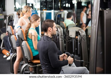 Group of young adults doing powerlifting on machines in fitness club