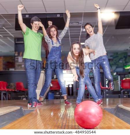 group of young adults having fun playing on the bowling alley