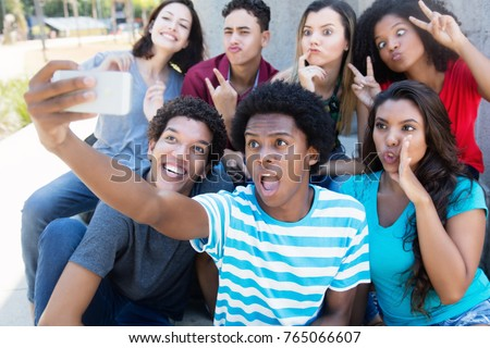 Group of young adults making funny selfie shots with phone outdoor in the summer