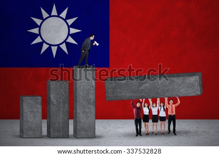Group of young asian businesspeople working together to build financial graph with Taiwan national flag backdrop - stock photo