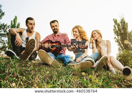 group of young attractive best friends having fan together. sitting on grass,playing on the guitar, singing and laughing.