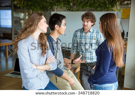 Group of young attractive people talking and discussing new project in meeting room - stock photo