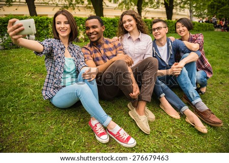 Group of young attractive smiling students dressed casual making selfie outdoors on campus at the university.
