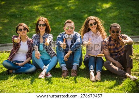 Group of young attractive smiling students dressed casual sitting on the lawn in park and resting.