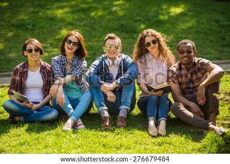 Group of young attractive smiling students dressed casual sitting on the lawn in park and studying. - stock photo