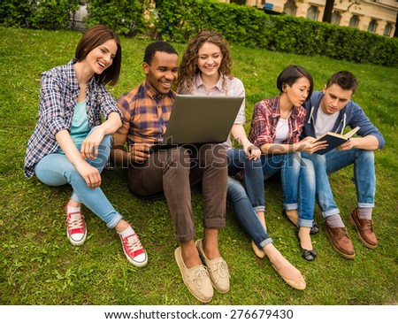 Group of young attractive smiling students dressed casual using laptop outdoors on campus at the university. - stock photo