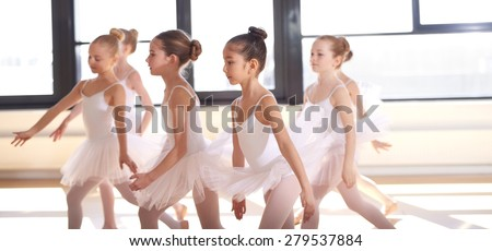 Group of young ballerinas performing a choreographed ballet as they train together at a ballet studio - stock photo