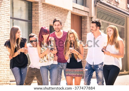 Group of young best friends having fun together walking on town street - Moment of technology interaction in everyday lifestyle - Internet connection spots outdoors - Soft desaturated filtered look - stock photo