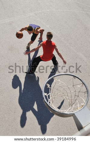 group of young boys who playing basketball outdoor on street with long shadows and bird view perspective - stock photo
