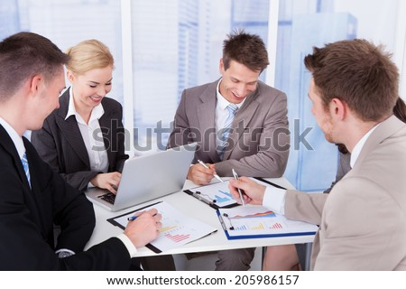 Group of young business people discussing at table in office