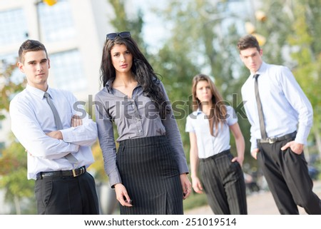 Group of young business people elegantly dressed standing outside enjoying the beautiful day, with a serious expression on their faces looking at the camera. - stock photo