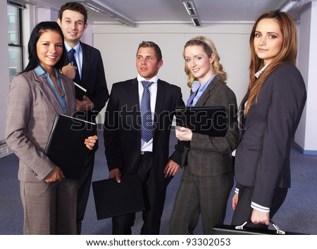 Group of 5 young business people, 3 females and 2 males all in business suits - stock photo