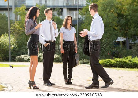 Group of young business people standing in a park near their company on the coffee break, talking to each other, enjoying the beautiful day. - stock photo