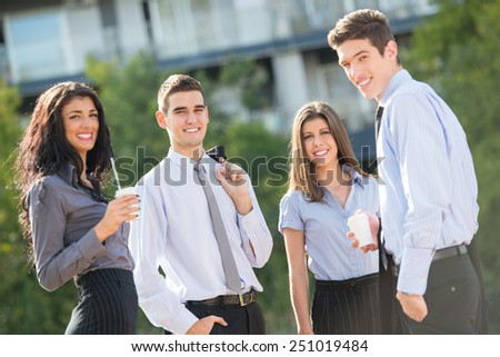 Group of young business people standing outside near their company on the coffee break, enjoying the beautiful day and with a smile on their faces looking at the camera. - stock photo