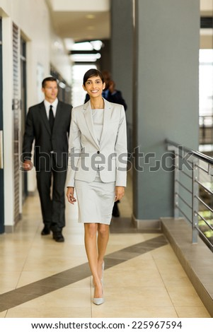 group of young business people walking in office passage - stock photo