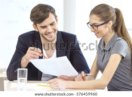 Group of young business people working with project. Young man and woman cheerfully smiling and working with documents. Office background