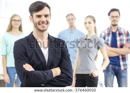 Group of young business people working with project. Young man cheerfully smiling and looking at camera. Business team standing behind him. Office background