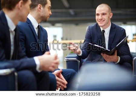 Group of young businessmen communicating at meeting - stock photo