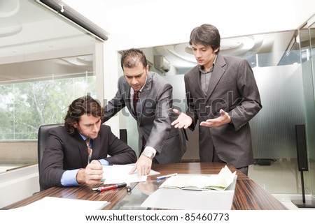 group of young businessmen having a serious and intense discussion in the business meeting. - stock photo