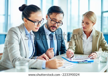 Group of young businesspeople discussing papers at meeting - stock photo