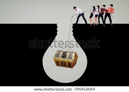 Group of young businesspeople finding a treasure chest in the soil and use a rope to get it together - stock photo