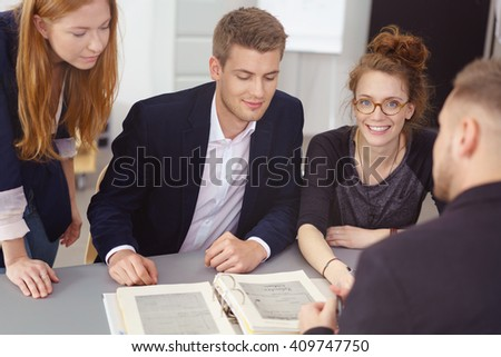 Group of young businesspeople in a meeting sitting grouped around a large office binder of notes having a brainstorming session - stock photo