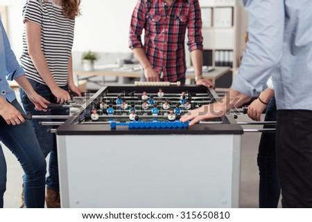 Group of Young Businesspeople Playing Table Soccer Game During their Free Time Inside the Office. - stock photo