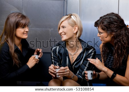 Group of young businesswomen sitting on couch in office lobby, drinking coffee, talking.