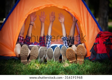Group of young campers lying down in a tent with their hands up - stock photo