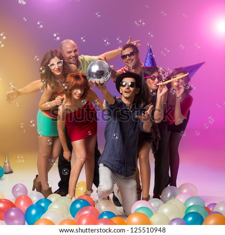 group of young caucasian beautiful people celebrating at a party surounded by colorful balloons and soap bubbles with a handsome guy between them kneeling and holding a disco ball - stock photo