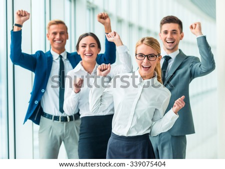 Group of young cheerful business people at the office - stock photo